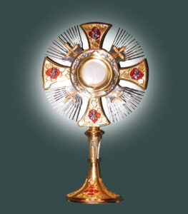 A simple monstrance, with Host, set on a dark slate blue background.